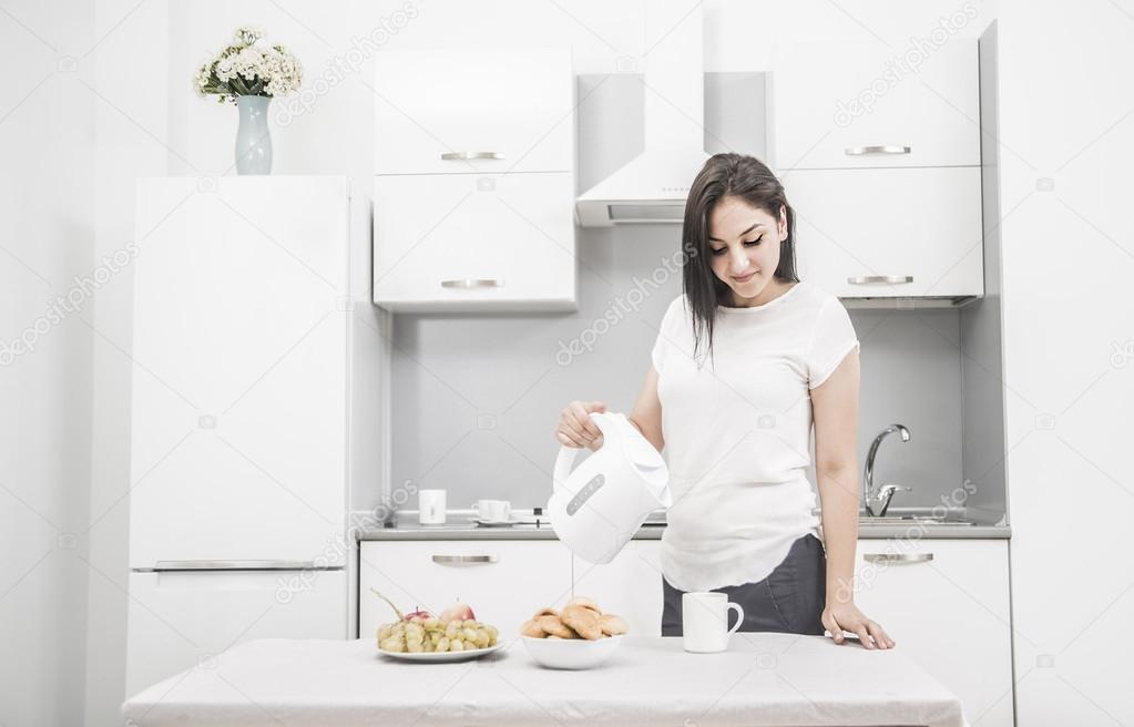 Frau mit Wasserkocher in der hand in der Küche stehen — Stockfoto ...