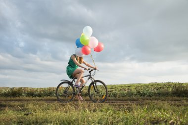 Young Girl riding bicycle with  balloons