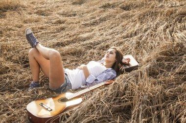 brunette girl laying near guitar