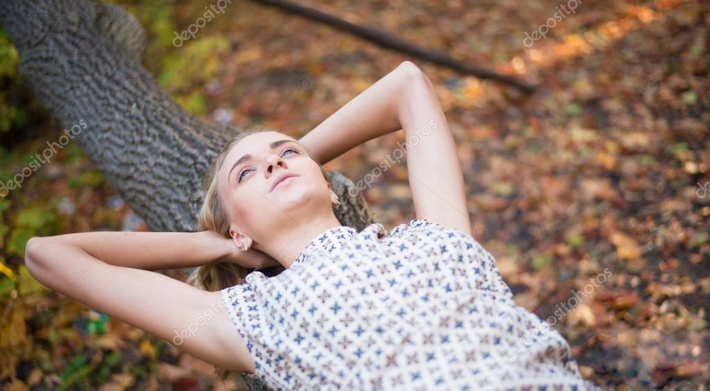 Chica en un tronco de árbol caído — Foto de Stock