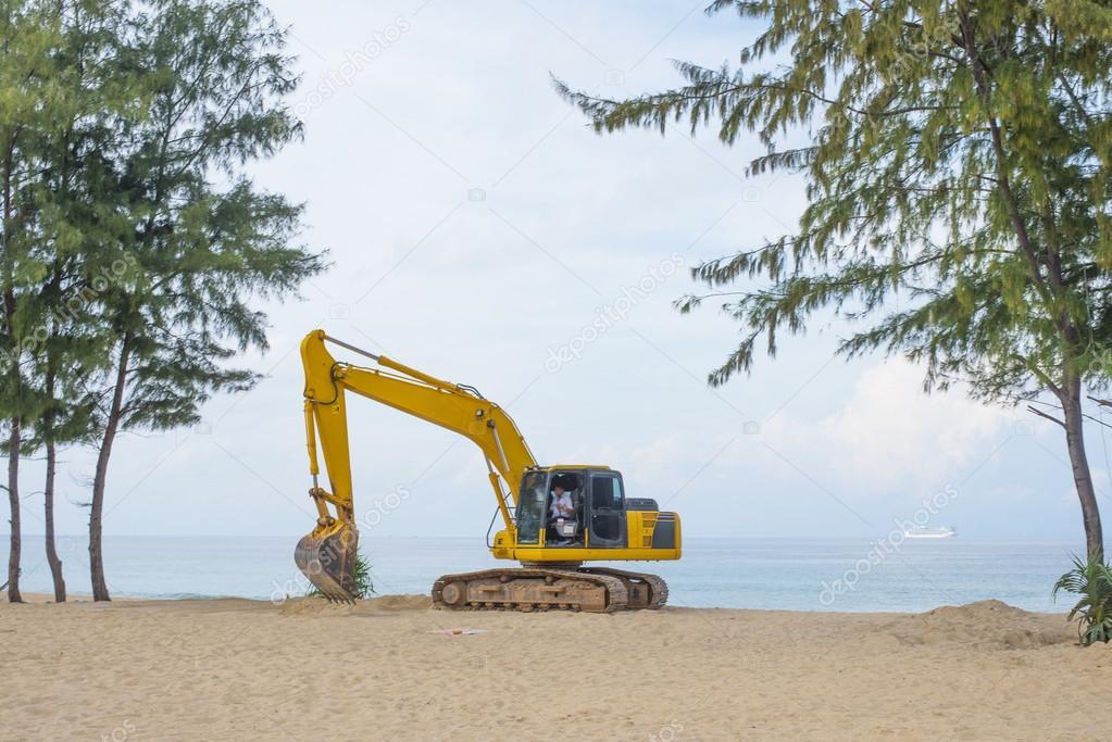 yellow Excavator on tropical beach