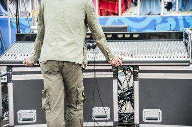 soundman stands against sound mixer control panel.
