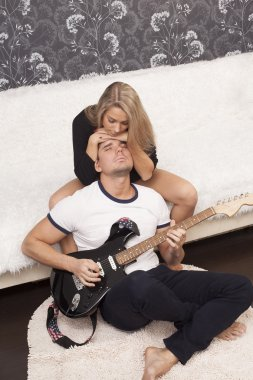 Portrait of  romantic couple with  guitar at  home