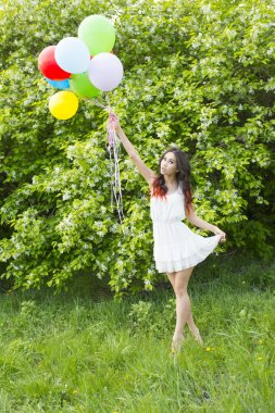 woman  holding color balloons