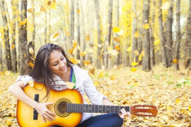 Portrait of young adult latin hispanic cute girl playing  acoustic guitar with flying leaves in windy air