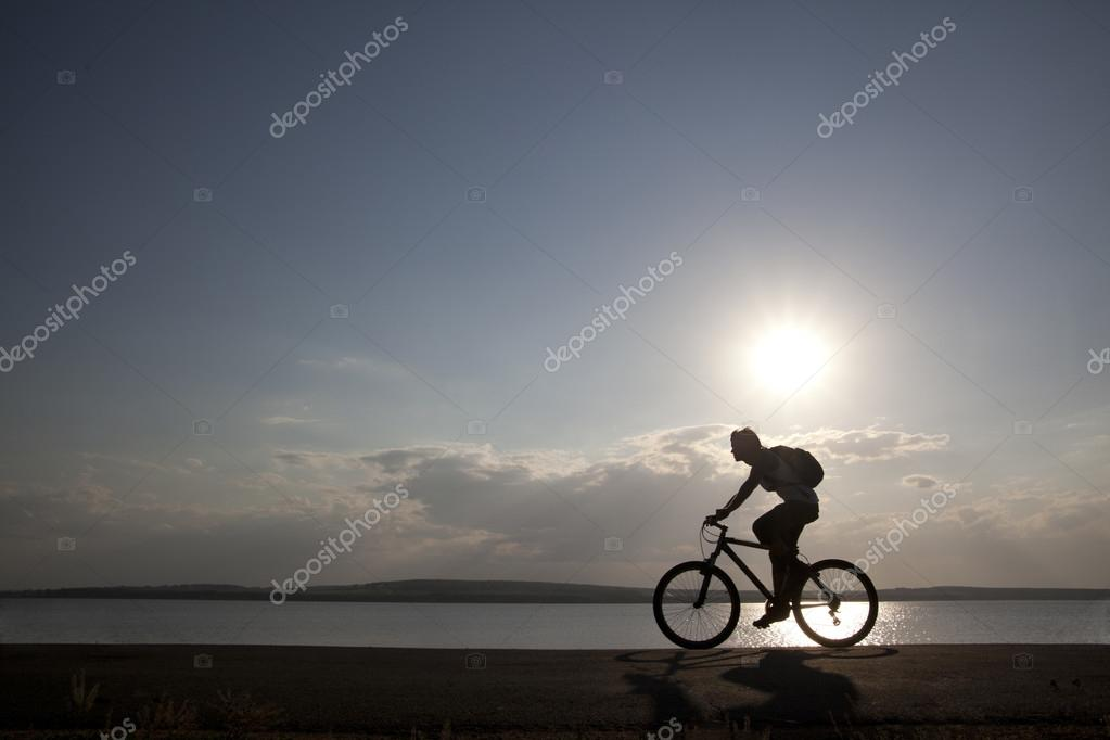 Silhouette of fit cyclist at sunset