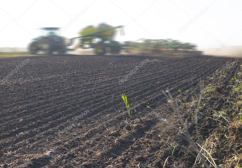 silhouette of tractor raking soil