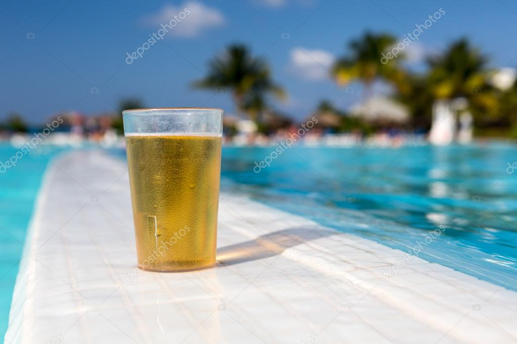 Glass of beer standing on the swimming pool