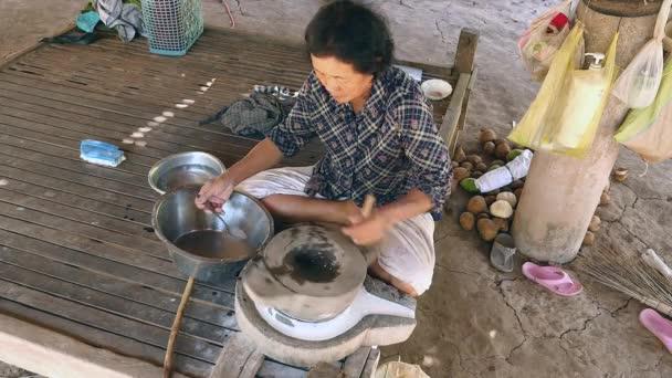žena pomocí rukou se obrátil millstone brousit mokré rýže pro výrobu namočené rýžové mouky a odnáší mlýnský kámen