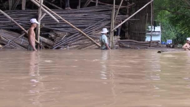 Arbeiter verladen Bambusstangen in einer überfluteten Lagerhalle