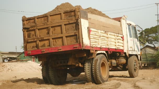 Truck loaded with dredged river sand at disposal site