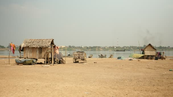 Small fishermens village on riverbank and dredging boat on river pumping riverbed sand as backdrop