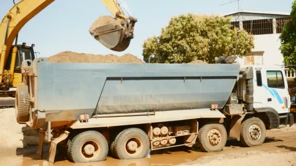 excavator loading sand into a dumper truck