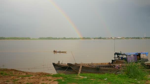 Duha nad řekou a malé rybářské lodi kolem vytěžená čluny svázaný na břehu řeky