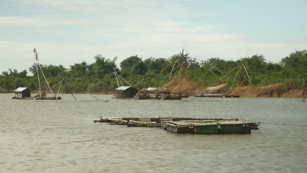 Čínské rybářské sítě a rybí farmy na jezeře