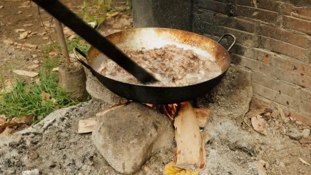 Keverés mély sertés belsejében egy fa bottal nyílt tűzön wok