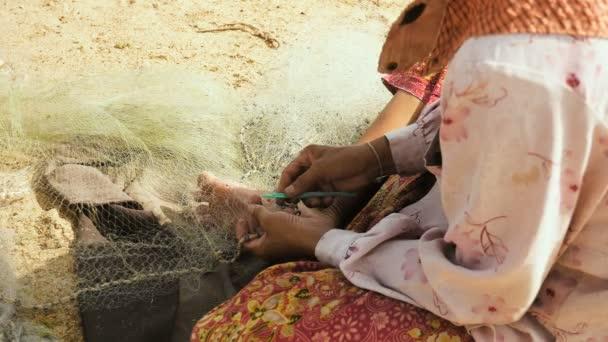 Detail na ženu sedět na břehu řeky opravit rybařské síti ručně