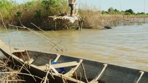 Rybář hází obsazení čisté v jezeře během větrný den