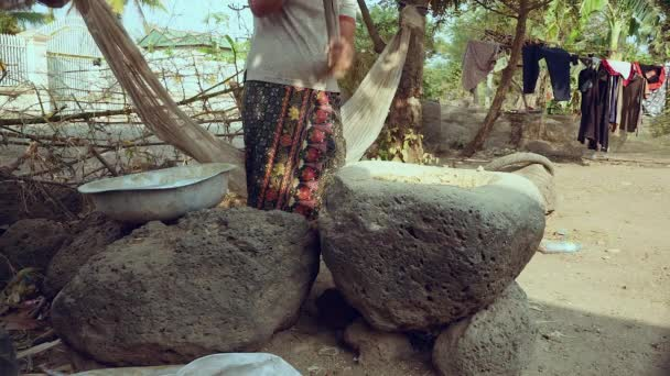 Woman pounding food using a wooden pestle with handle in a large stone mortar