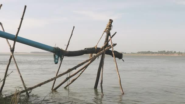 close-up of a piping system going down the river and hold with bamboo structure