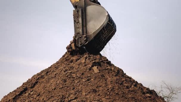 Rypadlo vybíjení a hromadí písek