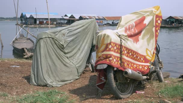 Motorbikes on the riverbank covered with blankets for sun and heat protection