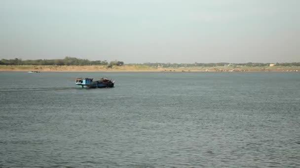 Vista posteriore della barca dragaggio procede lungo il fiume per pompare sabbia