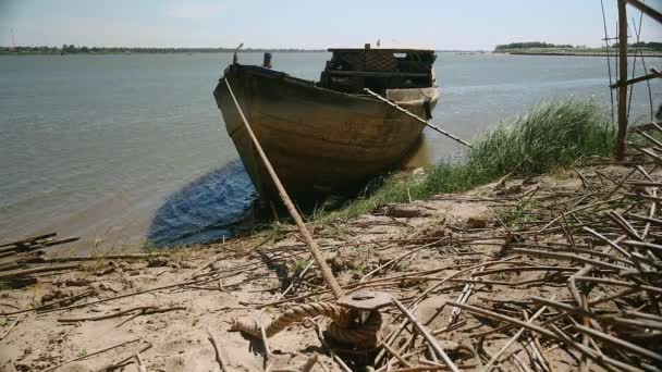 Starý dřevěný člun vytěžená vázána na břehu řeky