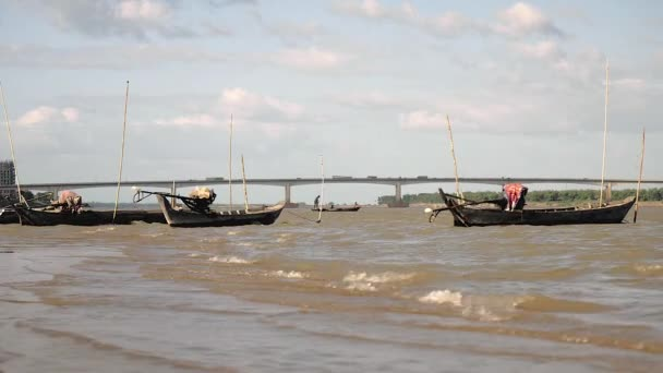 fishing boats tied up to to bamboo poles stuck in windy river and fisherman pulling net through the water in the background
