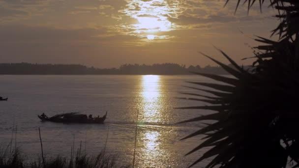 Small motorised boat proceeding on river at sunrise