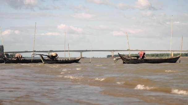 Fishing dugout canoes tied up to bamboo poles stuck in the windy river