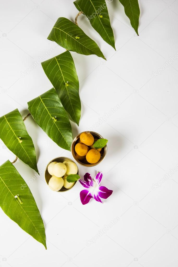Garland of mango leaves with indian sweet pedha and orchid ...