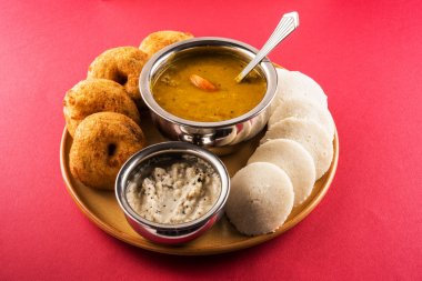 Sambar Vada & Idli with sambar, coconut chutney and red tomato chutney, Indian Dish served in earthen plate and bowl over white background, front view, isolated on white background