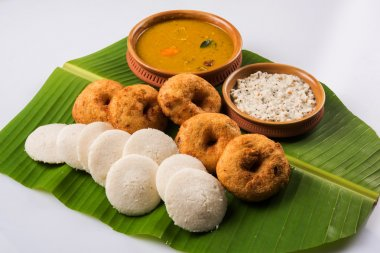 Sambar Vada & Idli with sambar, coconut chutney and red tomato chutney in earthen pots, served over green banana leaf over white background