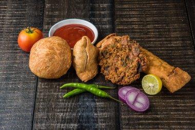 coriander vada or kothimbir vada, samosa, kachori, daal vada on brown wooden planks. indian assorted snacks. Indian snacks combination. Indian snacks group, indian favourite snacks, asian spicy snacks