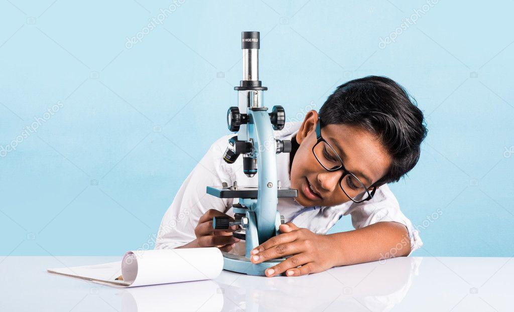 Indianerjunge und mikroskop asiatische junge mit mikroskop süßes