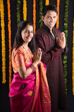 indian young couple praying in traditional cloths, indian newly married couple in namaskar or welcoming pose or prayer pose