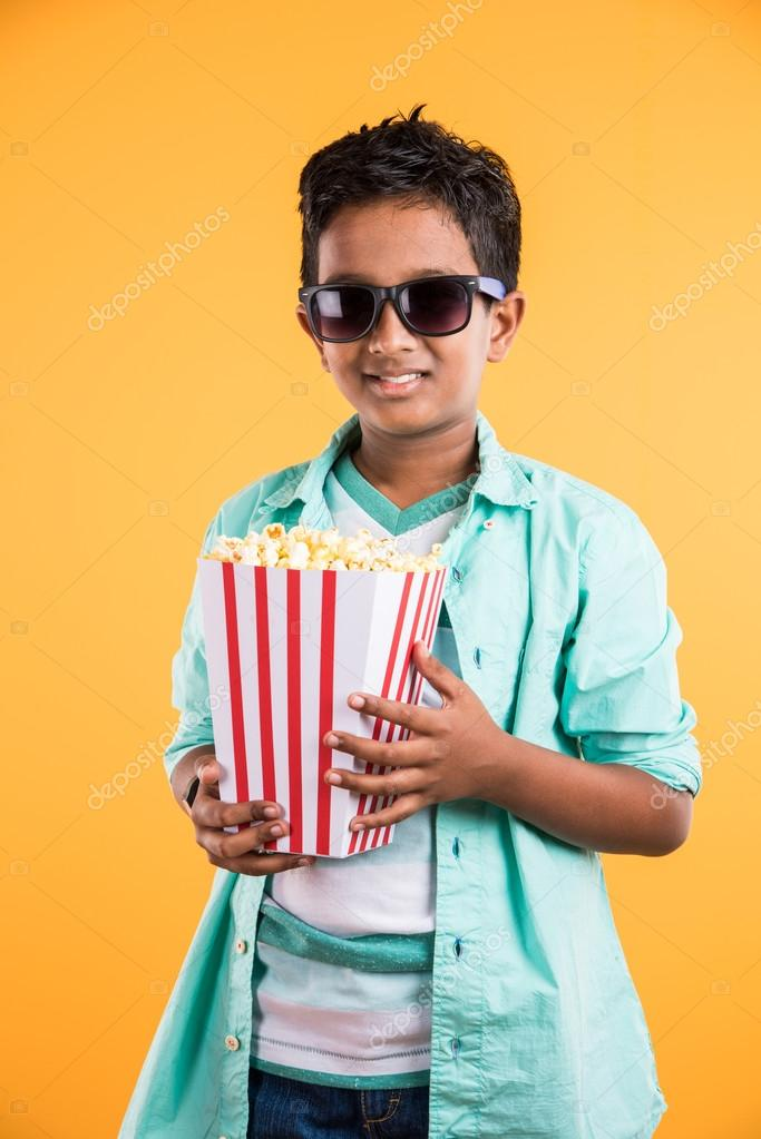 Joyful Indian Kid Holding A Big Box Of Popcorn And Looking At The Camera Isolated On