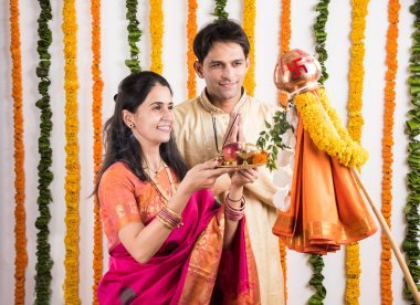 smart indian couple in traditional wear performing gudhi padwa puja, asian couple & puja thali, indian young couple with puja or pooja thali, hindu new year gudhi / gudi padwa, isolated