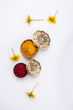 haldi or turmeric and kumkum or kum kum container  with flowers. Natural color powders are used while worshiping God and an at auspicious occasions.