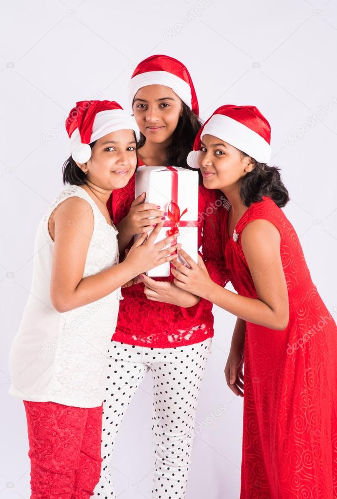 Three indian girls with santa hat and gifts in hand