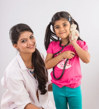indian girl child with young beautiful female doctor, indian doctor and baby girl, asian doctor with girl, isolated on gray background
