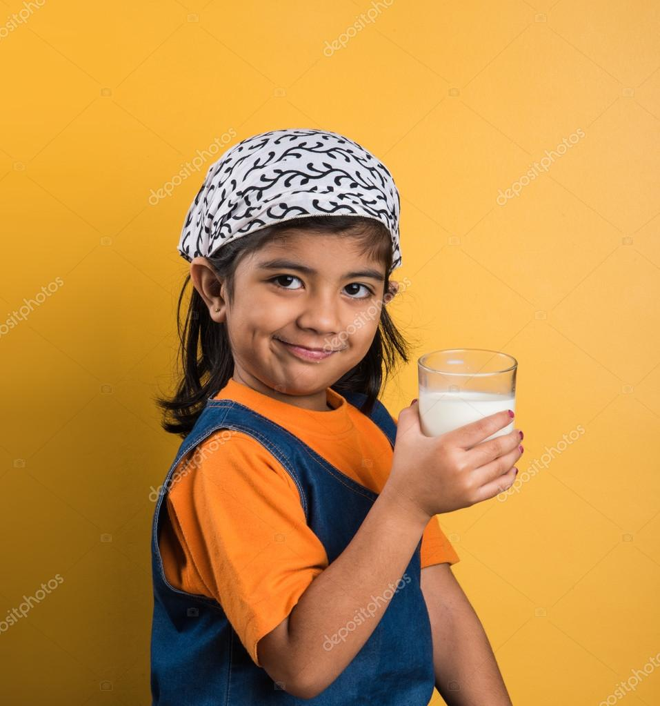 4 year old indian girl with a glass full of plain white milk indian girl and plain milk indian girl drinking milk asian girl and milk glass portrait