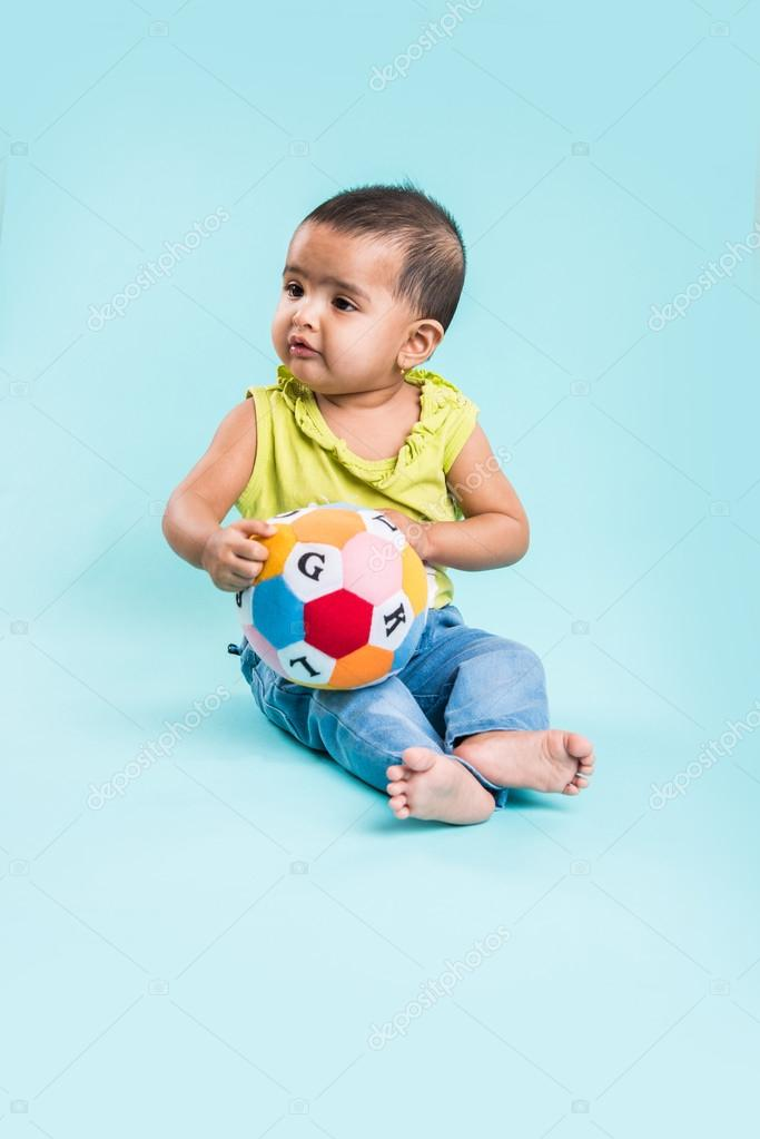 Indian Baby Girl Playing With Toys Or Blocks Or Soft Toys Over Blue