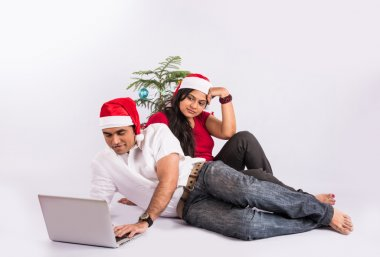 young indian couple with red santa hat, sitting close on white background with christmas tree, man busy on laptop and wife upset, busy man and sad wife on christmas time