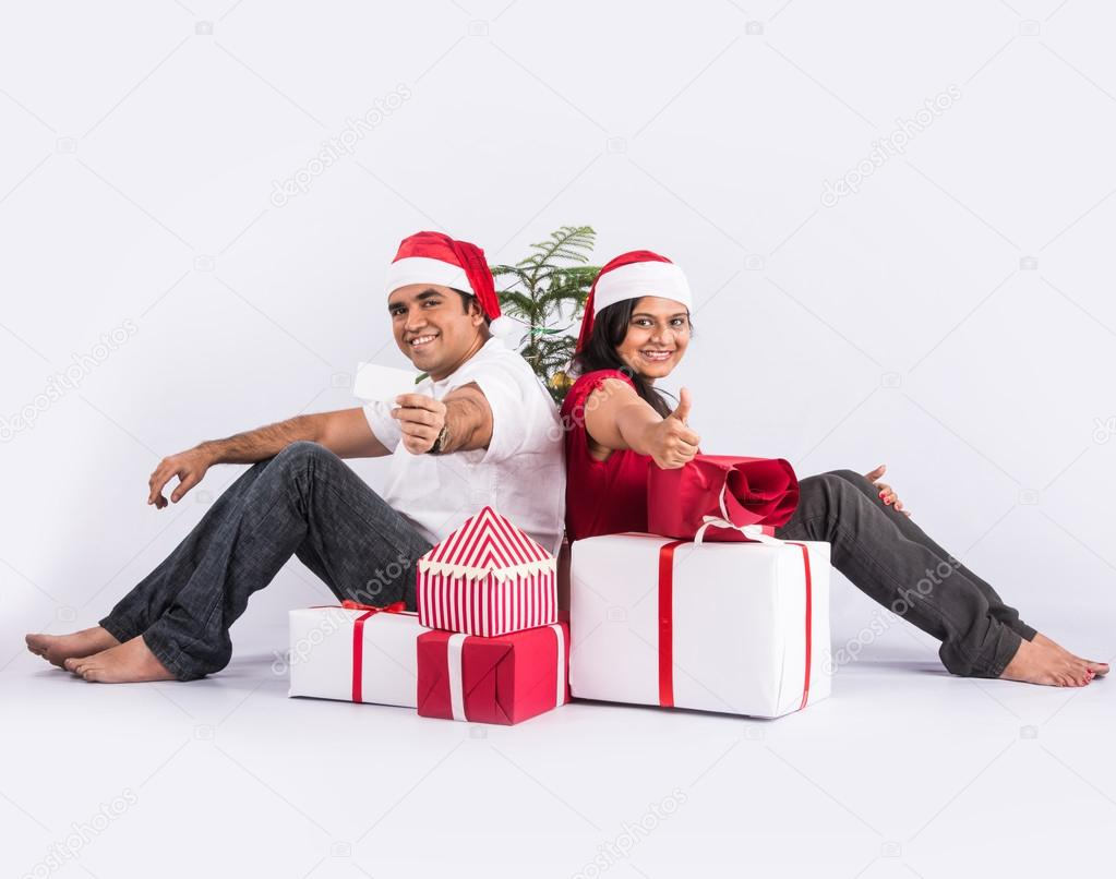 young indian couple sitting with with christmas gifts showing card ...