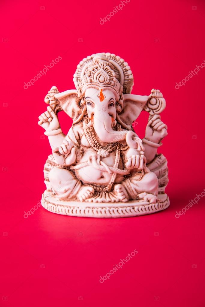 Statue Of Ganesha Idol Made Of White Marbal On Plain Bright Red
