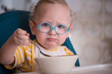 Little boy with glasses naughty and does not want to eat porridge