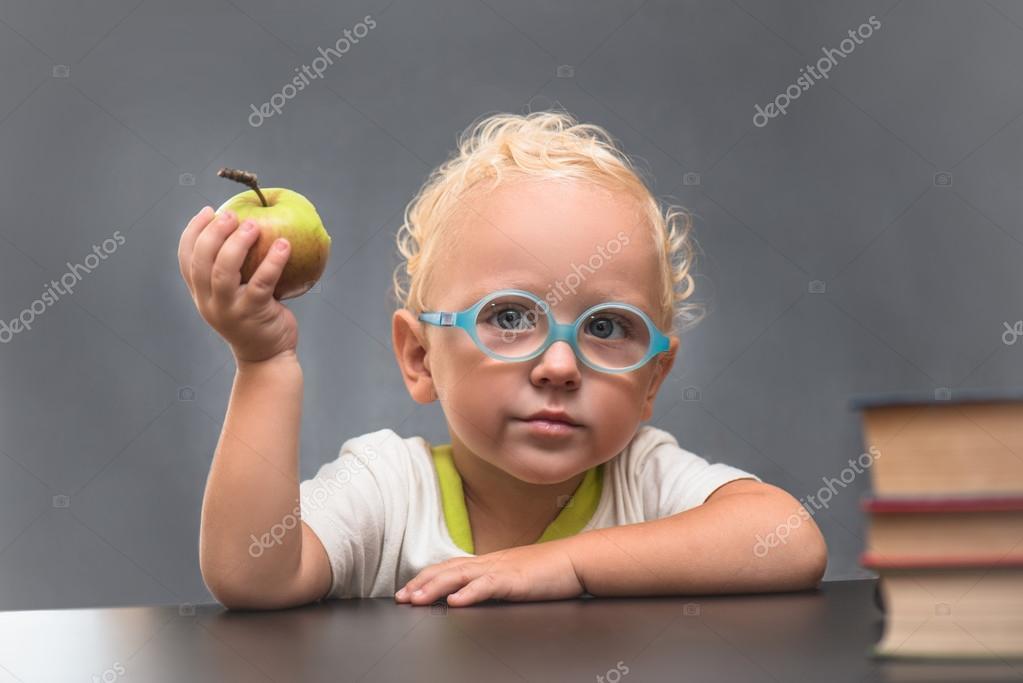 3cff6f5b6c6151 Kind met bril zit aan een tafel met boeken en apple — Stockfoto ...