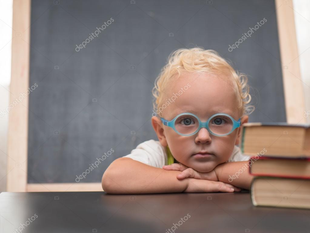 f71cfef768b9b3 Kind met bril zit aan een tafel met boeken — Stockfoto © kotmay ...